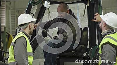 Retrato de um condutor de dois tratores caucasianos barbudos sentado na cabina e a falar com os seus colegas Trabalhadores em col filme