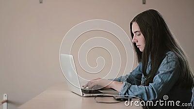 Retrato de um estudante do adolescente da menina que usa um portátil que surfa o Internet ao sentar-se na tabela em casa video estoque