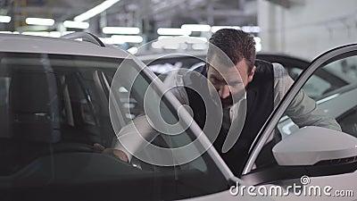 Retrato de um homem de negócios confiante caucasiano abrindo a porta do carro e tocando no automóvel Homem rico verificando seu v video estoque