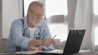 Retrato de um idoso de óculos com barba trabalhando em computador e analisa contas bancárias para pagar a sessão online em filme