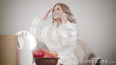 Retrato de uma alegre garota caucasiana no roupão branco sentado no sofá e falando ao telefone Linda mulher vídeos de arquivo
