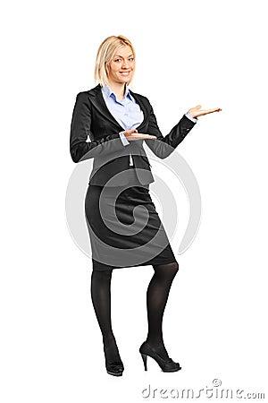Retrato de uma fêmea no terno que gesticula a boa vinda
