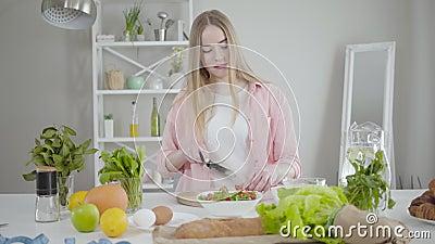 Retrato de uma garota caucasiana positiva fatiando tomate no quadro de corte e dança Mulher sorridente gostando de cozinhar no filme
