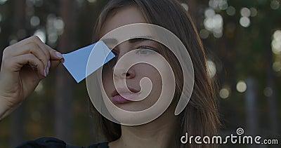 Retrato de uma garota caucasiana segurando fragmento de espelho quebrado Céu azul refletindo na fenda Mulher misteriosa com video estoque