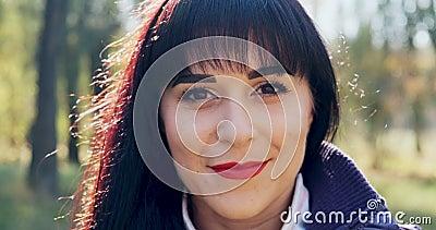 Retrato de uma jovem e atraente mulher brunet que sorri e olha para a câmera no parque de outono Mulher bonita e alegre video estoque