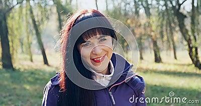 Retrato de uma jovem e atraente mulher brunet que sorri e olha para a câmera no parque de outono Mulher bonita e alegre filme