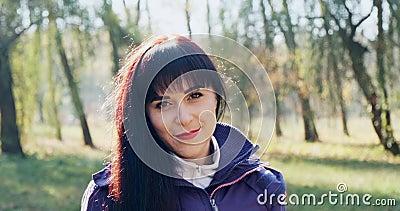 Retrato de uma jovem e atraente mulher brunet que sorri e olha para a câmera no parque de outono Mulher bonita e alegre vídeos de arquivo