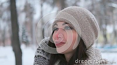 Retrato de uma linda garota de chapéu com pêlos escuros no inverno no parque e sorri bonito movimento lento filme