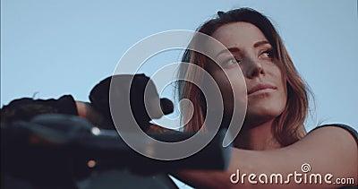 Retrato de uma menina que admire o por do sol que se senta em uma opinião inferior da motocicleta vídeos de arquivo
