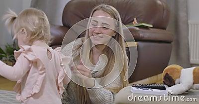 Retrato de uma mulher caucasiana feliz segurando a mão de uma garotinha e sorrindo Bebê bonito saindo com brinquedo macio Alegria video estoque