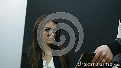 Retrato de uma mulher de negócios que senta-se no escritório e nos sinais os originais trazidos pelo empregado O fundo é preto vídeos de arquivo