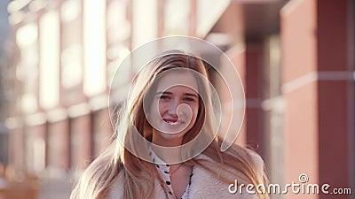 Retrato de uma senhora loura agradável nova que sorri à câmera que toca em seu cabelo ao acordar no centro da cidade no filme