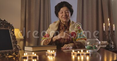 Retrato de un adivino caucásico positivo sentado en la mesa y sacando una carta La señora madura de Brunette en metrajes