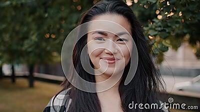 Retrato de un bonito estudiante asiático sonriendo solo en un parque urbano metrajes