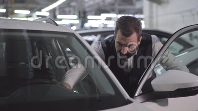 Retrato de un empresario caucásico seguro que abre la puerta de un coche y toca el automóvil Hombre rico revisando su vehículo almacen de video