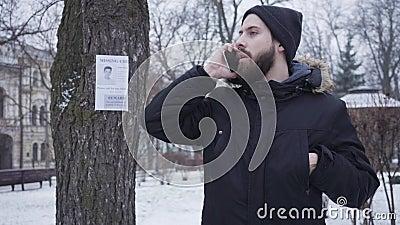 Retrato de un hombre barbudo caucásico parado al lado del anuncio de un niño desaparecido y llamando por teléfono Un tipo muy gua metrajes