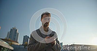 Retrato de un hombre milenario barbudo con el abrigo navegando y charlando en el teléfono móvil en la ciudad Toma de mano almacen de metraje de vídeo