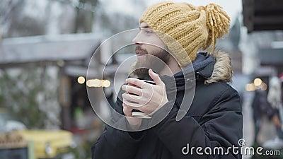 Retrato de un joven caucásico barbudo con un divertido sombrero amarillo y abrigo de invierno calentándose con café caliente al a metrajes