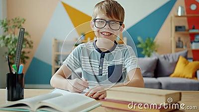 Retrato de un niño alegre sonriendo mirando a la cámara haciendo los deberes en casa almacen de metraje de vídeo