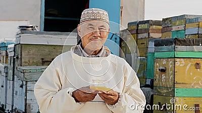Retrato de un viejo granjero sonriente que sostiene un contenedor con miel, producción orgánica metrajes