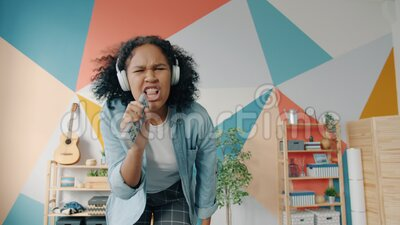 Retrato de una atractiva chica con auriculares cantando en control remoto bailando en casa almacen de video
