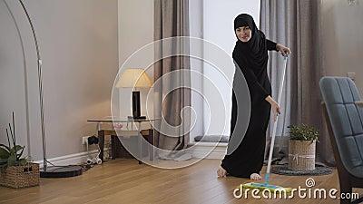 Retrato de una joven musulmana limpiando el suelo Joven con hijab negro usando trapos para hacer tareas domésticas Cultura orient metrajes