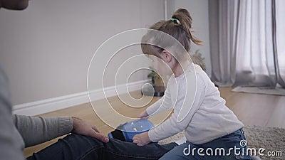 Retrato de una linda chica caucásica ayudando a un joven irreconocible a poner guantes de boxeo La hija de Brunette está gastando almacen de metraje de vídeo