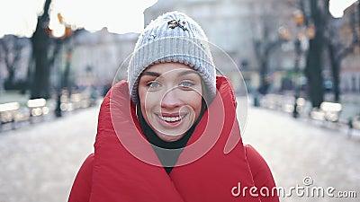 Retrato de una muchacha imponente en sombrero gris y capa roja que sonríe mientras que ella se coloca en la calle antes de decora almacen de video