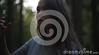 Retrato de una mujer hermosa mirando lejos parado en el bosque verde profundo La chica caminando en el bosque Conexión metrajes