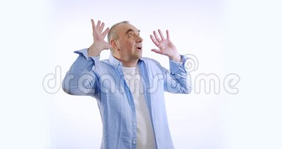 Retrato del anciano conmocionado, hombre asustado, grita de miedo haciendo gestos sobre un fondo blanco cerrado Concepto de emoci almacen de metraje de vídeo