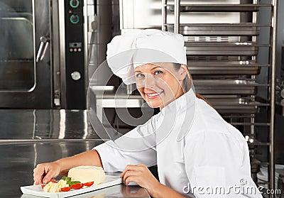 Cocinero de sexo femenino con el plato en el contador