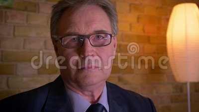 Retrato del hombre de negocios mayor en traje formal que mira en la cámara que es seria en fondo casero acogedor metrajes