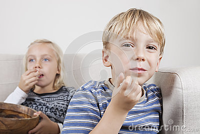 Retrato del muchacho joven con la hermana que ve la TV y que come las palomitas