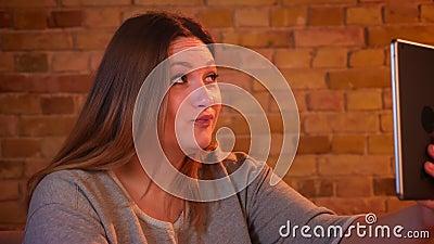 Retrato del primer del modelo femenino rechoncho risueñamente que habla en videochat en la tableta en atmósfera casera acogedora metrajes
