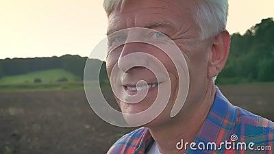 Retrato del viejo granjero que mira la cámara y el campo sonriente, cultivado durante mañana en fondo, feliz y alegre almacen de metraje de vídeo