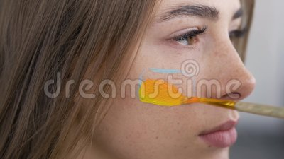 Retrato detalhado de uma jovem e bonitinha Pintura artística no rosto da garota usando pincel macio pequeno Conceito de arte de c video estoque