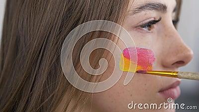Retrato detalhado de uma jovem linda mulher Pintura artística no rosto da garota usando pincel macio pequeno Arte corporal vídeos de arquivo