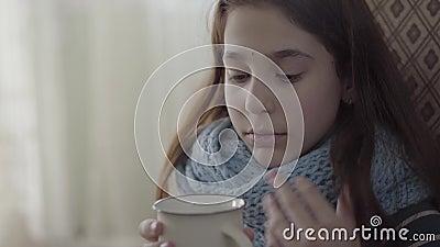 Retrato do adolescente envolvido no len?o morno que guarda um copo do ch? quente nas m?os A menina sente m?, ? doente e tem vídeos de arquivo