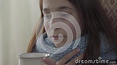 Retrato do adolescente envolvido no len?o morno que guarda um copo do ch? quente nas m?os A menina sente m?, ? doente e tem video estoque