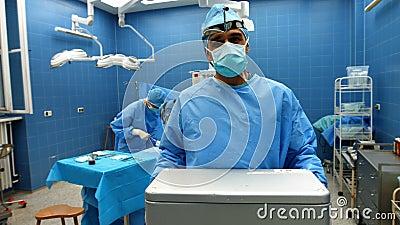 Retrato do cirurgião que guarda a caixa de gelo quando colegas que executam a operação filme