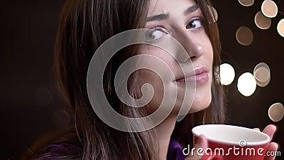 Retrato do close up da fêmea caucasiano bonita nova com um copo do chá morno que gerencie para a câmera que sorri e pensativament video estoque