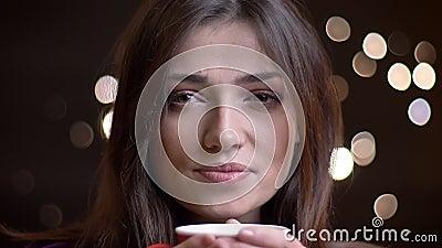 Retrato do close up da fêmea caucasiano bonita nova que come um copo do chá morno que sorri e que olha a câmera filme