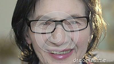 Retrato do close up da mulher madura feliz que olha na câmera lentamente filme