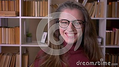 Retrato do close up do estudante fêmea caucasiano novo nos vidros que sorri com a confusão que olha a câmera na faculdade filme