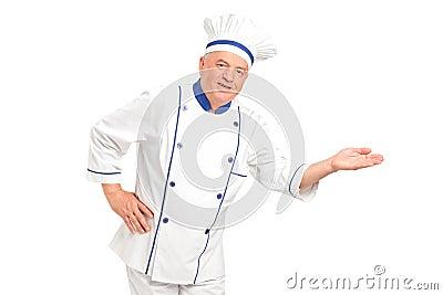 Retrato do cozinheiro chefe de sorriso que gesticula a boa vinda
