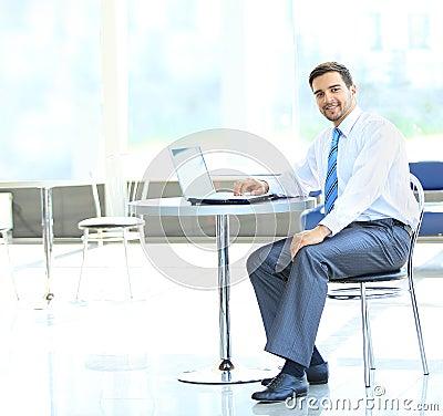 Retrato do gerente ocupado que datilografa no portátil
