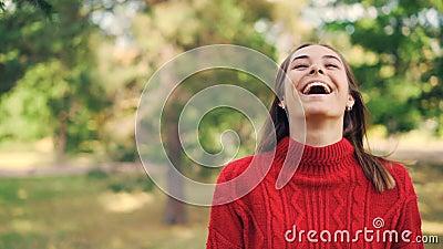 Retrato do movimento lento da menina alegre na camiseta morna que está no parque com sorriso contente, rindo e olhando vídeos de arquivo