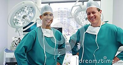 Retrato dos cirurgiões masculinos que estão com mãos nos quadris na sala de operação vídeos de arquivo