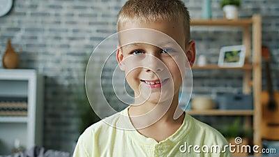 Retrato estreito de doce menino sorrindo em pé sozinho em um apartamento video estoque