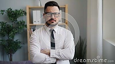 Retrato lento do moton do homem de negócios sério com os braços cruzados no escritório vídeos de arquivo